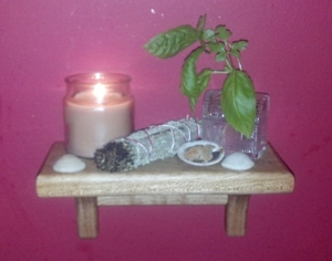 My altar for Hestia is on a small shelf next to my stove. It holds a candle, a sprig of basil, a sage smudge stick and some shells.